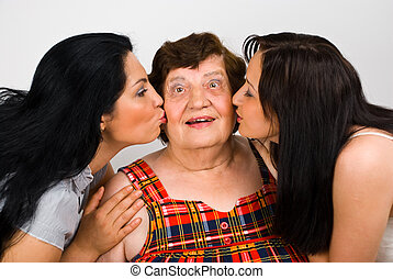 Grandma kissed by two granddaughters