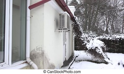 Ice pile frozen under heat pump system on house wall in...