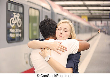 Couple hugging at the train station - Interracial couple...