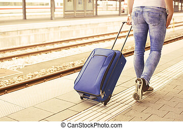 Woman at the train station - Womans legs with suitcase at...