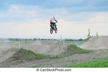 athlete in motocross - biker making a stunt and jumps in the...