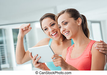 Happy girlfriends using a tablet - Happy girl friends...