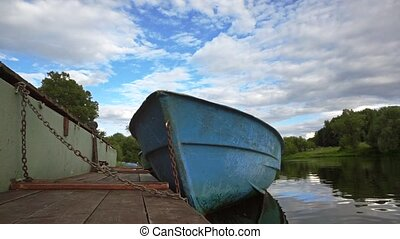 River pier with moored empty blue boat slow motion shot -...