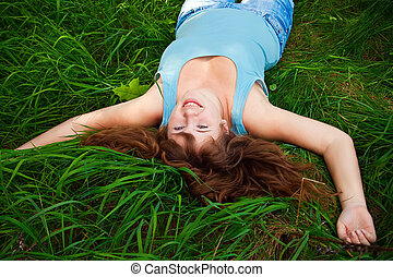 Laughing Woman On A Grass - portrait of a beautiful happy...