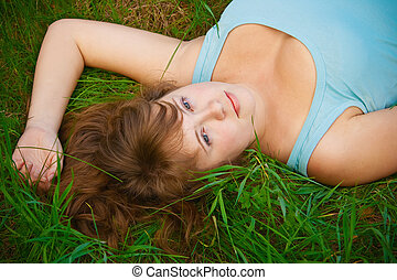 Woman On A Grass - portrait of a beautiful female lying on a...