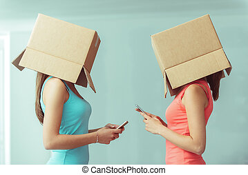 Lack of communication - Adolescent girls with boxes on their...