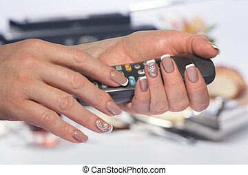 Female hands with French manicure hold the handset
