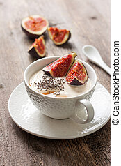 yogurt with pieces of fig, chia seeds, honey in a white cup...