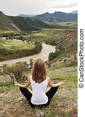 Young Woman Outdoor Meditation. Sitting on the Mountain.