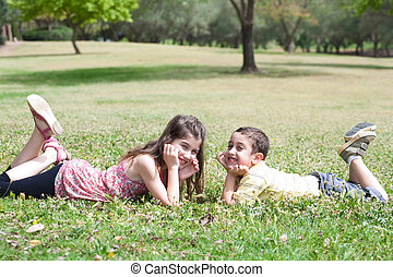 Cute children lie down on green grass and looking eachother...