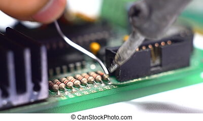 Close up shot soldering a circuit board with a soldering...