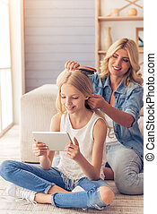 Mom and daughter - Attractive teenage girl is using a tablet...