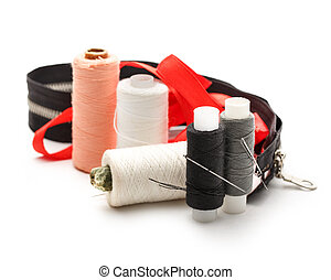 Thread bobbins and needles on white background