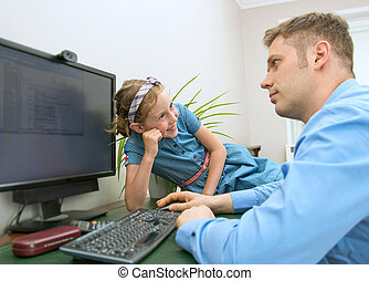Little girl disturbing her dad while he is working at home.