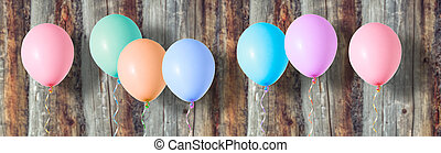 Multicoloured air flying balloons on wooden background