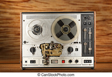 Old reel tape recorder on wooden background