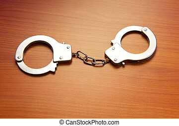 Metal handcuffs on the wooden background