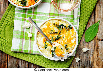 Chicken Spinach Cauliflower casserole on a dark wood...