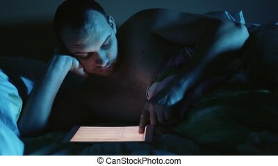 Young man looks tablet pc late at night before sleep in the...