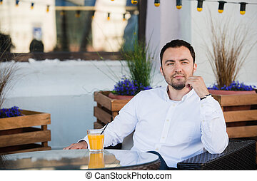 Handsome businessman is waiting for client in cafeteria. He...