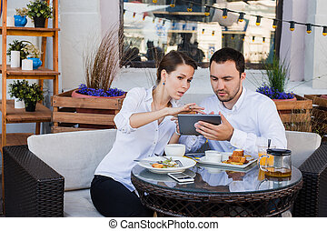 Business people looking at digital tablet in cafe during a...