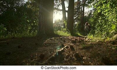 Long hair brunette girl walking towards camera in sunset...