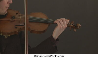 Classical Violin Player - Violinist plays against a black...
