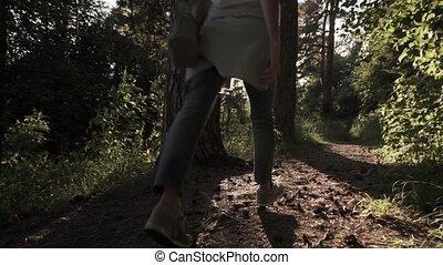 Brunette girl walking away from camera in sunset coniferous...