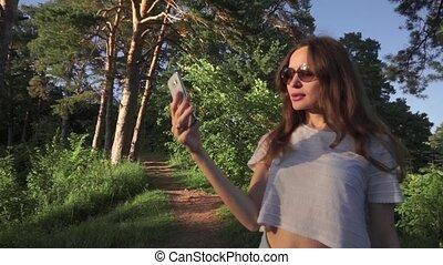 Young long hair brunette girl in sunglasses making selfie...