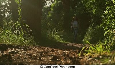 Brunette girl walking towards camera in sunset coniferous...