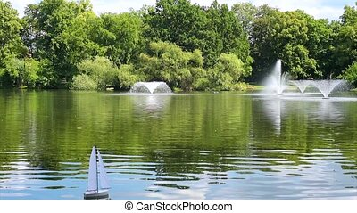 Sailing boat in pond - Radio controlled boat sailing on...
