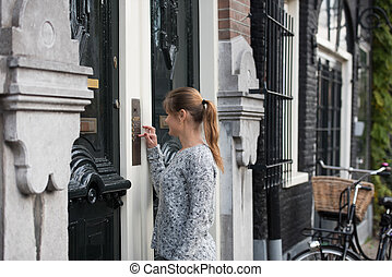girl in Amsterdam - young woman in front of entrance door,...