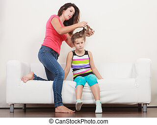 Mother combing hair for daughter - Mother combing daughter,...