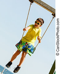 Boy playing swinging by swing-set - Rest and relax for...