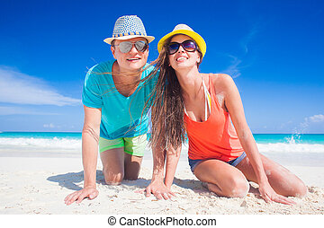 long haired girl in straw hat blowing a kiss on tropical caribbean beach