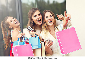 Group of girlfriends shopping in the city with credit card...
