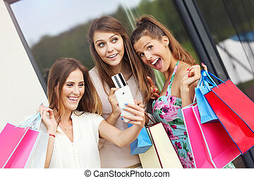 Group of girlfriends shopping in the city with credit card -...