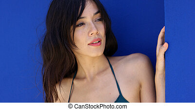 Attractive young brunette wearing halter top and having long...