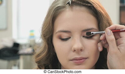 Makeup artist making make-up for a young model