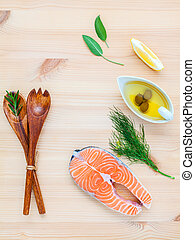 Raw salmon fillet in the white bowl with ingredients olive...