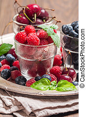 small glasses of fruit containing cherry, blueberry and...