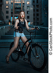 Biker girl on a bicycle. - Woman biker on bike rides through...