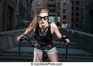 Woman in sunglasses on the bike. - The woman in glasses on a...