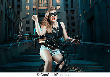 Woman with whip on a bicycle. - Woman with a whip in biker...