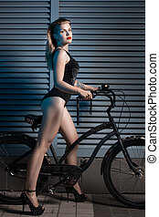 Woman with a bicycle cruiser. - Woman night outdoors holding...