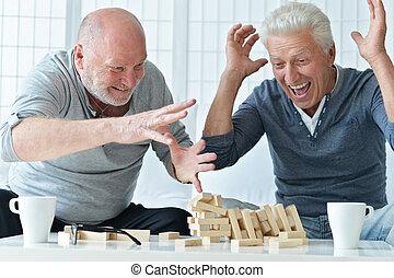 senior men playing board game - two senior men having fun...