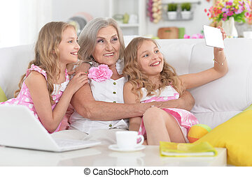 woman with tweenie girls doing selfie - Old woman with...