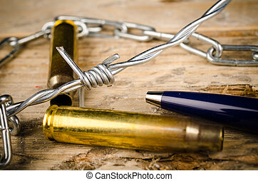 Freedom of press - Bullets and barbed wire around a pen, a...