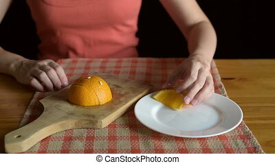 Putting orange segments on a plate - Woman putting orange...