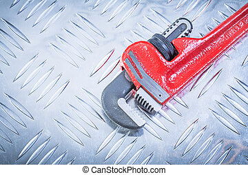 Adjustable monkey wrench on grooved metal background constructio